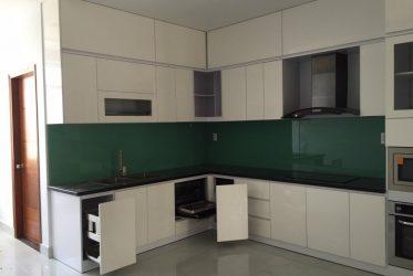 Tủ bếp gỗ acrylic chữ L màu trắng kính màu xanh rêu TBARL-030